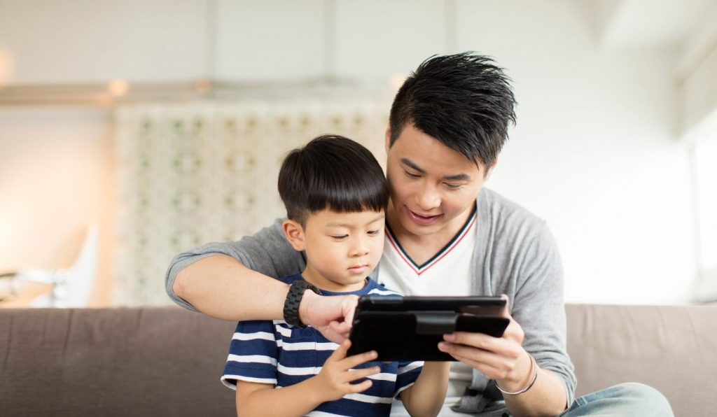 dad assisting child while looking at an electronic tablet