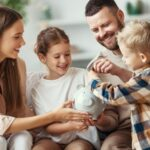 family is smiling while using a piggy bank